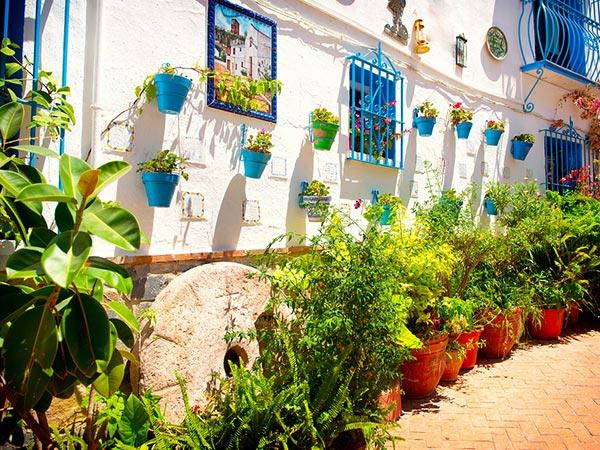 Calle de Torremolinos. Casa con pared encalada con macetas y azulejos