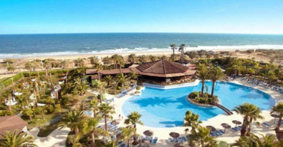 Hotel de playa en la costa Andaluza con piscina y rodeado de palmeras